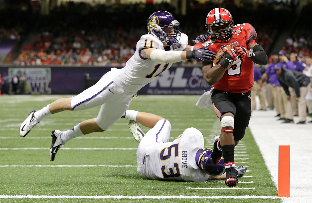 . Louisiana-Lafayette wide receiver Harry Peoples (9) scores a touchdown as East Carolina defensive back Damon Magazu (11) and linebacker Jeremy Grove (53) defend in the first half of the New Orleans Bowl, an NCAA college football game in New Orleans, Saturday, Dec. 22, 2012. (AP Photo/Dave Martin)