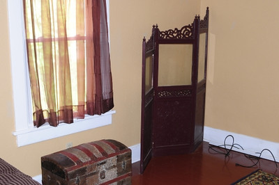 The larger of the two bedrooms on the second floor features a wood floor and two windows.