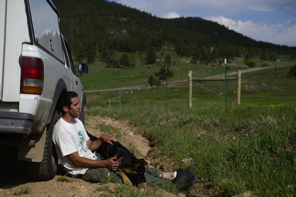 . John Orlando, 28, sits with his family\'s dog, Otto, and watches as a fire burns in the hills west of Evergreen, Colorado. A fire started early in the afternoon on June 3, 2013 and by 3:30 p.m., residents of the surrounding area were told to evacuate. Many packed horses and other animals in trailers and drove them to nearby meadows. (Photo by AAron Ontiveroz/The Denver Post)
