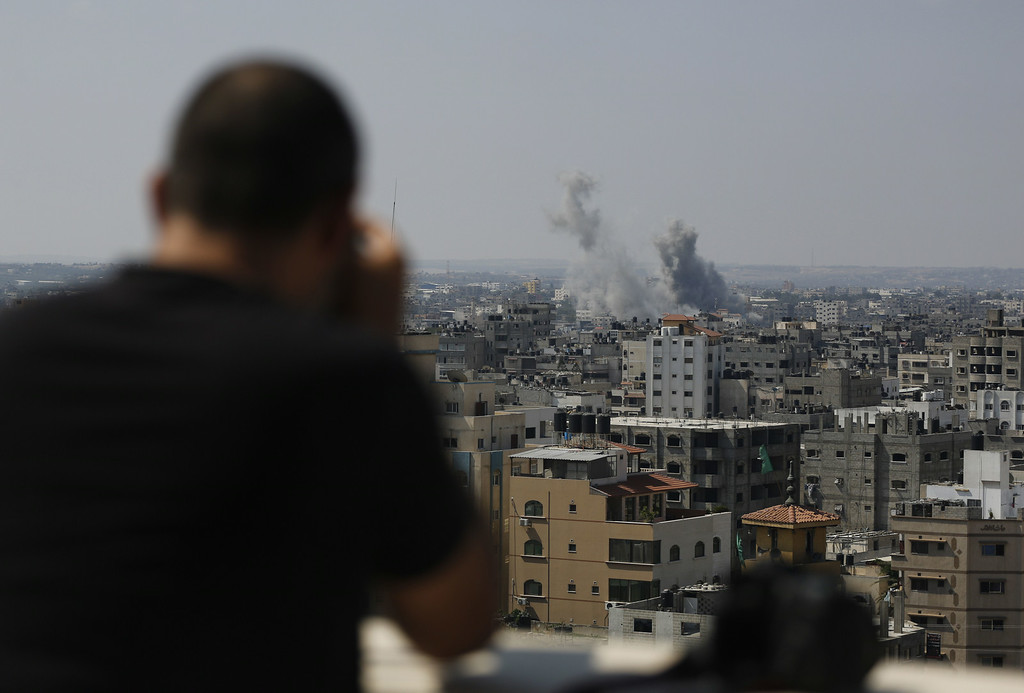 . A Palestinian photographer takes photos of smoke rising following an Israeli air strike on a home in Gaza City on August 23, 2014. Israel kept up the pressure on Hamas in Gaza, carrying out multiple air strikes that killed six Palestinians, five of them from the same family, as Egypt readied to call new truce talks. MOHAMMED ABED/AFP/Getty Images