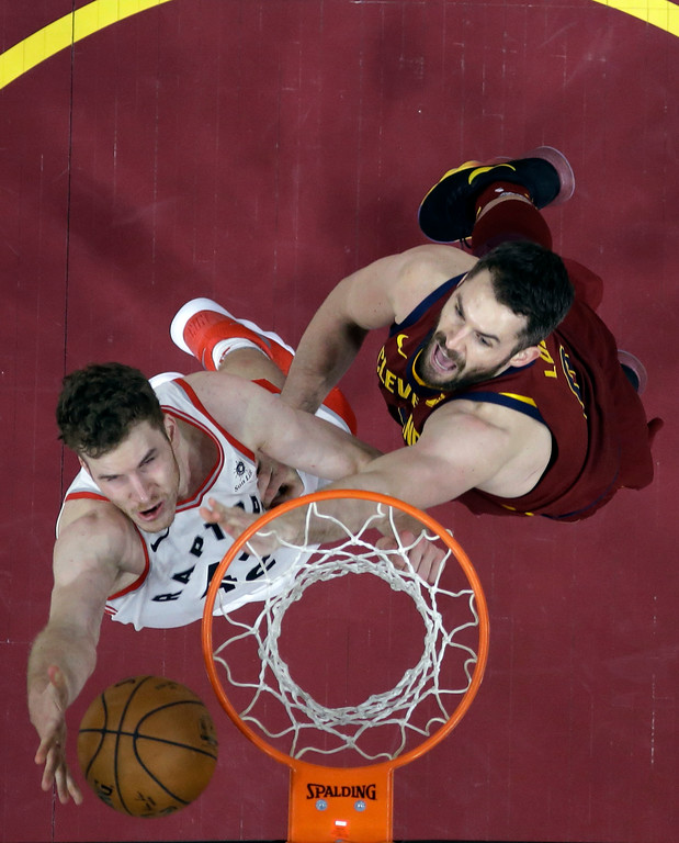 . Toronto Raptors\' Jakob Poeltl, left, drives to the basket against Cleveland Cavaliers\' Kevin Love during the second half of an NBA basketball game Wednesday, March 21, 2018, in Cleveland. The Cavaliers won 132-129. (AP Photo/Tony Dejak)