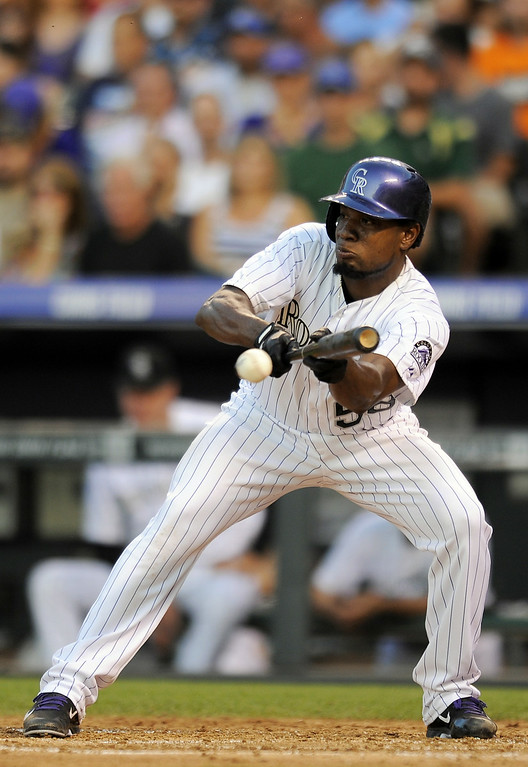 . Colorado Rockies Yohan Flande puts down a sacrifice bunt in the fourth inning of a baseball game against the Washington Nationals on Tuesday, July 22, 2014, in Denver. (AP Photo/Chris Schneider)