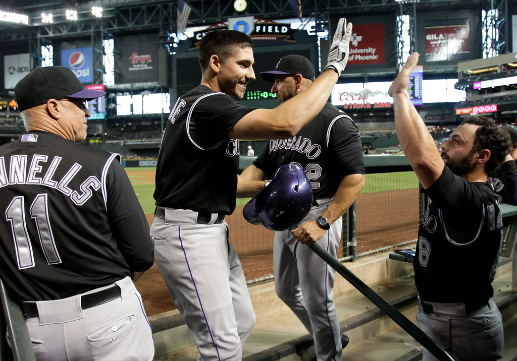 . Colorado Rockies\' Matt McBride, second from left, celebrates with teammates after hitting a second-inning home run during a baseball game against the Arizona Diamondbacks, Saturday, Aug. 30, 2014, in Phoenix. (AP Photo/Rick Scuteri)