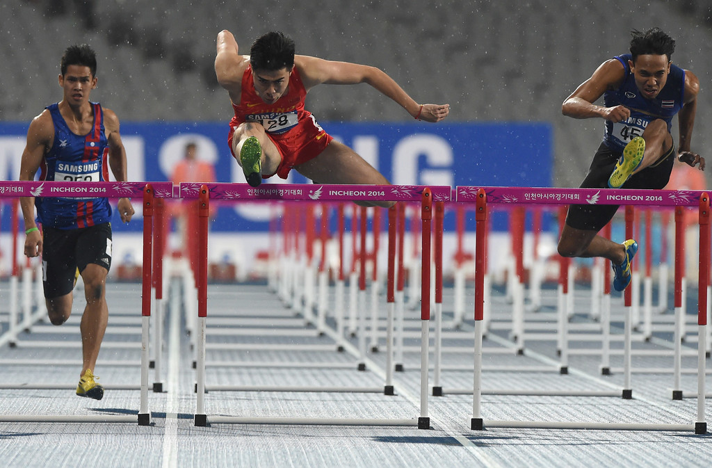 . (L-R) Laos\' Anousone Xaysa, China\'s Xie Wenjun and Thailand\'s Jamras Rittidet compete in the heats of the men\'s 110m hurdles athletics event during the 17th Asian Games at the Incheon Asiad Main Stadium in Incheon on September 28, 2014.  PHILIPPE LOPEZ/AFP/Getty Images