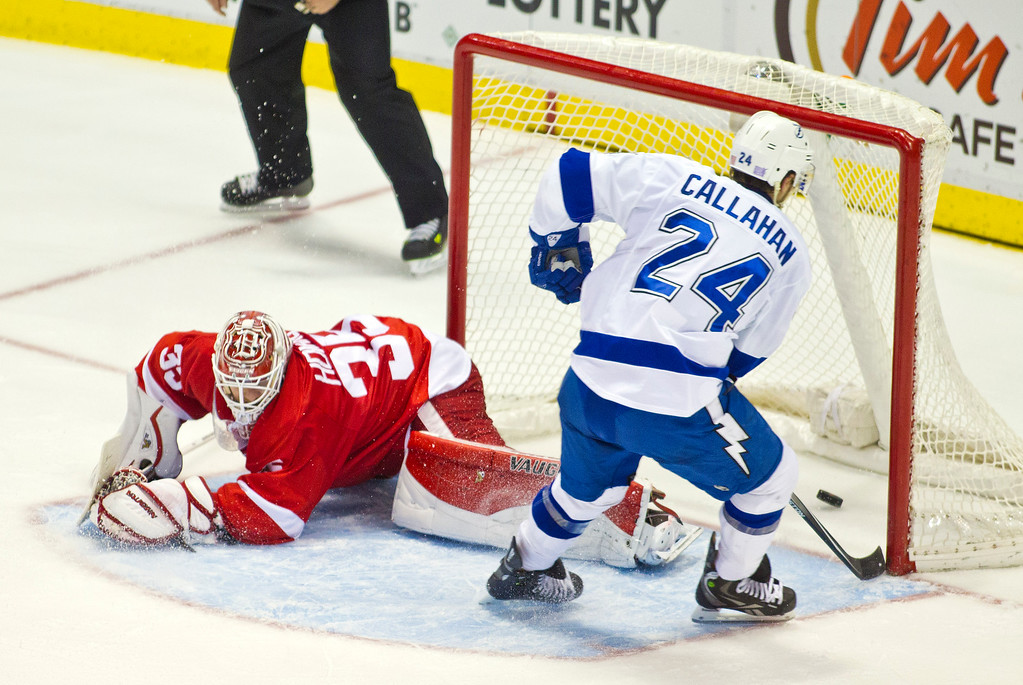 . Tampa Bay Lightning forward Ryan Callahan (24) scores the game-winning shootout goal on Detroit Red Wings goalie Jimmy Howard (35), to give a 4-3 victory to Tampa Bay in the NHL hockey game in Detroit, Mich., Sunday, Nov. 9, 2014. (AP Photo/Tony Ding)