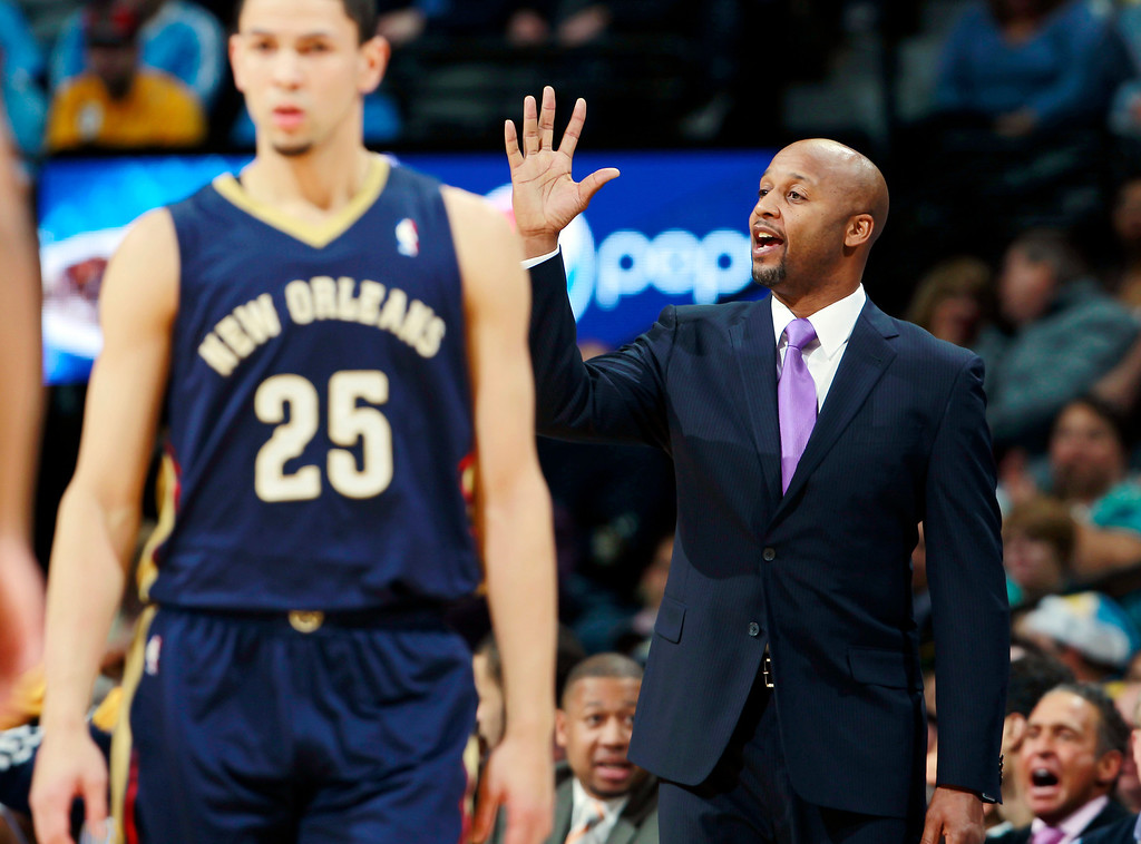 . New Orleans Pelicans guard Austin Rivers, front, walks away as Denver Nuggets head coach Brian Shaw motions to his team in the first quarter of an NBA basketball game in Denver on Sunday, Dec. 15, 2013. (AP Photo/David Zalubowski)
