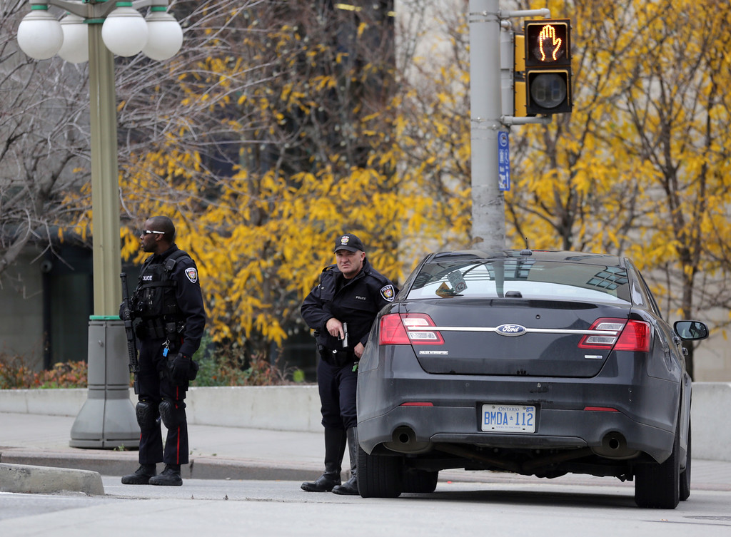. Police officers stand guard on Wellington St. in downtown, October 22, 2014 in Ottawa, Canada. Officials are investigating multiple reports of shootings and suspects after at least one gunman shot a Canadian soldier and then entered Canada\'s Parliament building.   (Photo by Mike Carroccetto/Getty Images)