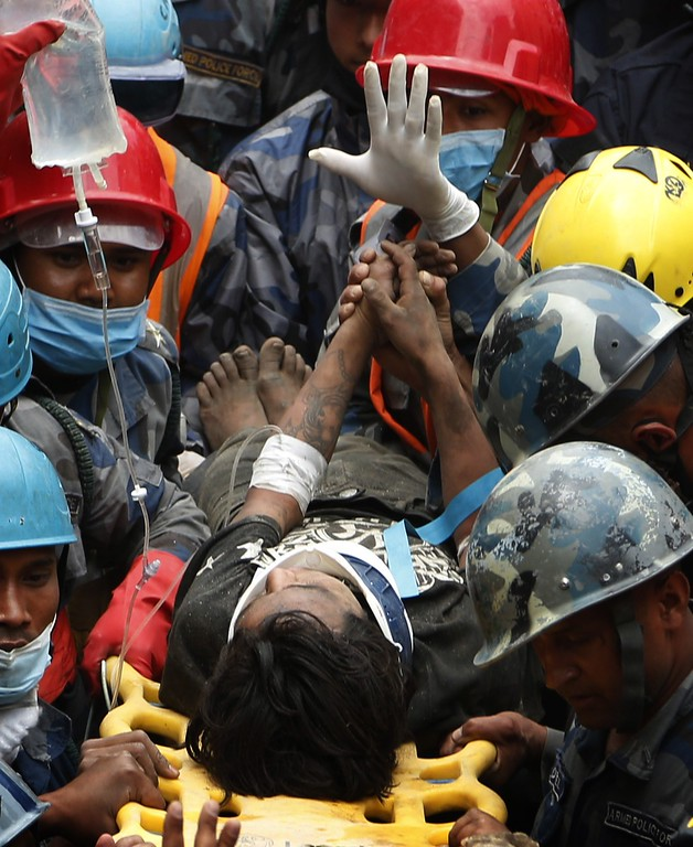 . Nepalese police personnel carry earthquake survivor Pemba Tamang on a stretcher after his rescue from a destroyed hotel building in Kathmandu on April 30, 2015. Rescuers pulled a 15-year-old boy alive from the rubble of Nepal\'s earthquake April 30, bringing a rare moment of joy to the ruined capital Kathmandu, five days after a disaster which killed nearly 6,000 people. The rescue of Pemba Tamang, who told AFP that he stayed alive by eating ghee, was hailed as a miracle and greeted with cheers from crowds of bystanders who massed to watch the drama unfold at a ruined guesthouse.   AFP PHOTOSTR/AFP/Getty Images