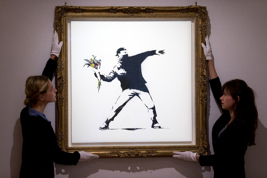 ". Gallery assistants adjust ""Love is in the Air\"" by British graffiti artist Banksy ahead of its sale at Bonhams auction house in London on June 24, 2013. The spray paint work by the celebrated secretive artist is estimated to fetch between 70,000-100,000 British pounds (107,000 - 154,000 USD). (JUSTIN TALLIS/AFP/Getty Images)"