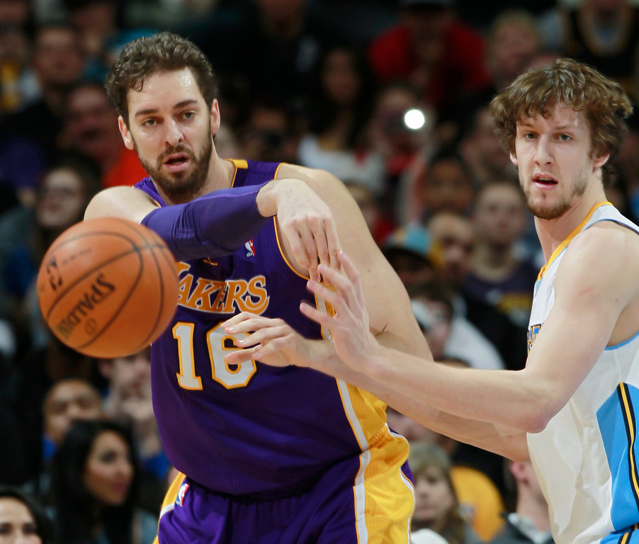 . Los Angeles Lakers center Paul Gasol, left, of Spain, passes ball as Denver Nuggets forward jan Vesely, of the Czech Republic, covers in the fourth quarter of the Nuggets\' 134-126 victory in an NBA basketball game in Denver on Friday, March 7, 2014. (AP Photo/David Zalubowski)