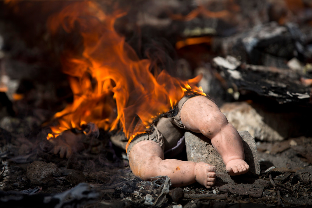 . A doll is burned with other leavened items by Ultra-Orthodox Jewish men in final preparation for the Passover holiday in Jerusalem, Friday, April 22, 2016. Jews are forbidden to eat leavened foodstuffs during the Passover holiday that celebrates the biblical story of the Israelites\' escape from slavery and exodus from Egypt. (AP Photo/Oded Balilty)