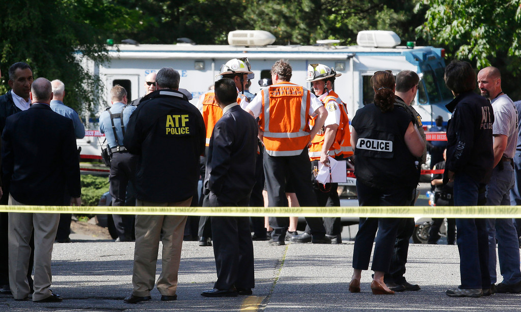 . Authorities gather at the scene of a shooting Thursday, June 5, 2014 at Seattle Pacific University in Seattle. A lone gunman armed with a shotgun opened fire Thursday in a building at the small Seattle university, killing one person before he was subdued by a student as he tried to reload, police said. Police say the student building monitor disarmed the gunman and several other students held him until police arrived at the Otto Miller building. (AP Photo/Ted S. Warren)