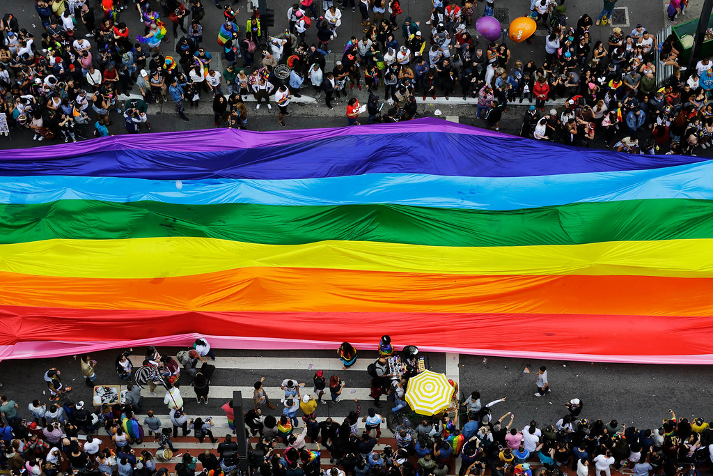 . Revelers extend a flag during the annual gay pride parade in Sao Paulo, Brazil, Sunday, June 3, 2018. (AP Photo/Nelson Antoine)