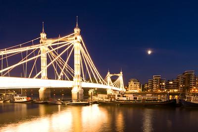 Illuminated Albert Bridge seen from Chelsea Embankment at night, London, United Kingdom