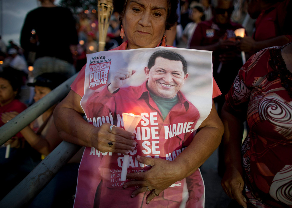 . A woman holds a candle along with a poster of Venezuela\'s President Hugo Chavez at a candlelight vigil to pray for his health in Caracas, Venezuela in this Feb. 22, 2013 file photo. Venezuela\'s Vice President Nicolas Maduro announced the death of President Hugo Chavez in Caracas on March 5, 2013. (AP Photo/Ariana Cubillos)