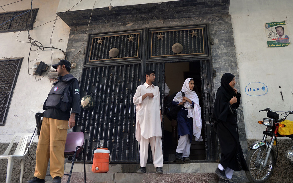 . A Pakistani policeman stands guard as female students leave the school of child activist, Malala Yousafzai, in Mingora the capital of Swat Valley on September 23, 2013. In Malala Yousafzai\'s home town in Pakistan, school friends hope to see her win the Nobel Peace Prize this week -- but they dream in secret, under pressure from a society deeply ambivalent about the teenage activist.  Malala, who survived being shot by the Taliban on October 9 last year, has become a global ambassador for education, feted by celebrities and politicians around the Western world.   AAMIR QURESHI/AFP/Getty Images