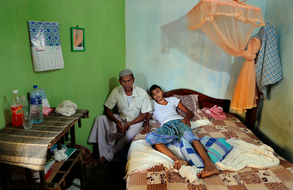 . In this Wednesday, June 25, 2014 photo, Sri Lankan Muslim youth Mohamed Namaz, right, rests in his bedroom as he receives treatment for gun shot injuries in Darga Town in Aluthgama about 50 kilometers (31 miles) south of Colombo, Sri Lanka. Namaz, a 17-year-old Muslim, still has a bullet lodged in his thigh. The onslaught by the Bodu Bala Sena, a hardline Buddhist group that has gained thousands of followers in recent years, killed two Muslims and injured dozens more last month in the worst religious violence Sri Lanka has seen in decades. (AP Photo/Eranga Jayawardena)