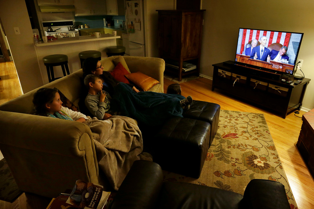 . Diana Meza-Ehlert watches as President Barack Obama delivers his State of the Union address with daughter Eliana, left, son Lucas, second from left, and daughter Anais, right, in their home Tuesday, Jan. 20, 2015, in San Diego. Obama\'s next-to-last State of the Union address spoke to the economic woes of beleaguered low-income Americans and the country\'s shrinking middle class. (AP Photo/Gregory Bull)