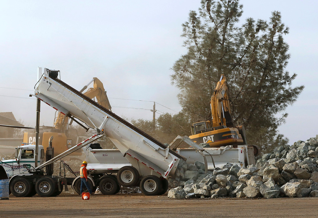 . A dump truck unloads rocks at a staging area near the Oroville Dam, Monday, Feb. 13, 2017, in Oroville, Calif. State officials have discussed using helicopters to drop loads of rock on the damaged emergency spillway of the dam. (AP Photo/Rich Pedroncelli)