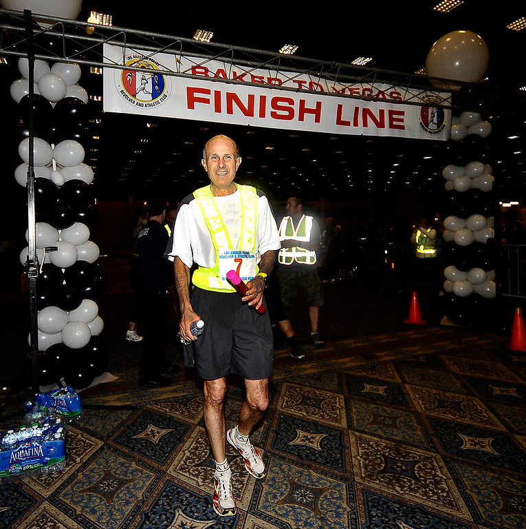 . LA county sheriff commander Lee Baca crosses the finish line as he ran the last part of the race for his department during the 26th annual Baker to Vegas run that ended  Sunday at the Hilton Hotel in Las Vegas. Baker CA. April 18,2010   (Gene Blevins/LA DailyNews)