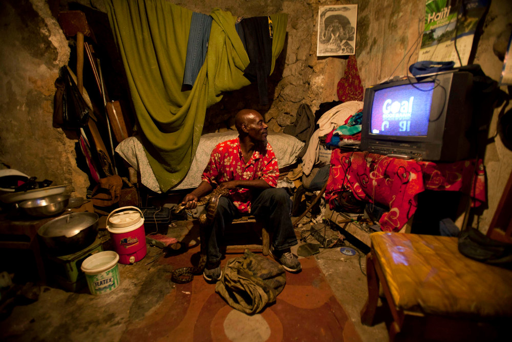 . In this Jan. 24, 2013 photo, snake handler Saintilus Resilus watches a soccer game at his home while holding a snake, and a bag of more snakes lays at his feet, as he prepares for his street performances using snakes, for which he charges money, in Petionville, Haiti. Resilus is one of millions of people scrambling to get by in a country where the unemployment rate hovers around 60 percent and most get by on $2 a day. (AP Photo/Dieu Nalio Chery)