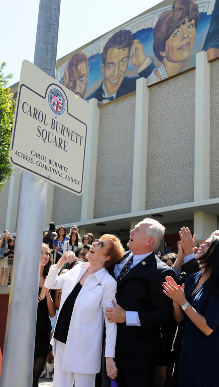 """. Carol Burnett and Councilman Tom LaBonge look up at her new street sign, while her picutre appears on a mural on the front of Hollywood High School. Burnett, the award-winning actress, comedienne and best-selling author, was honored by the City of Los Angeles for her lifetime achievements with the naming of Carol Burnett Square at the intersection of Highland Avenue and Selma Avenue. The Square is adjacent to Hollywood High School where Burnett attended. Students from the school choir, \""""H2O\"""" sang �I�m so glad we had this time together,� before Burnett and LA City Councilman Tom LaBonge unveiled her street sign. Hollywood, CA 4/18/2013(John McCoy/Staff Photographer"""