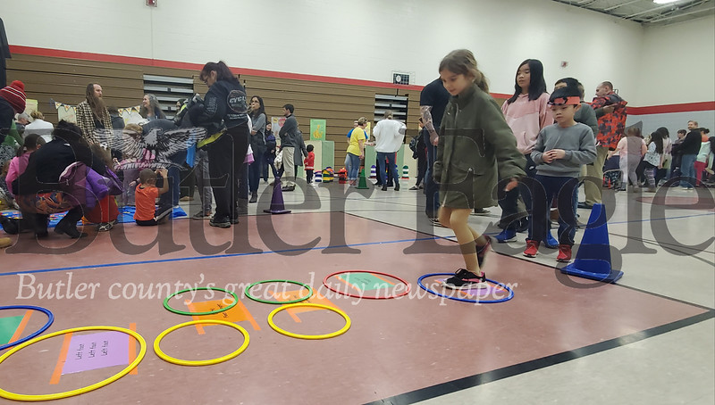 Abby Smith, 3rd grade, jumps from hoop to hoop at the Dr. Suess celebration Wednesday night at Slippery Rock Area Elementary School. Also pictured is volunteer Ashley Shea, junior at Slippery Rovk High School. Nathan Bottiger/ Butler Eagle