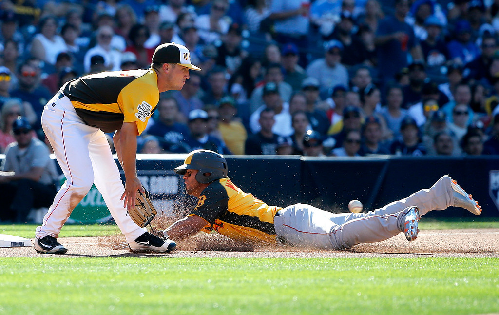 . World Team\'s Yoan Moncada, right, of the Boston Red Sox, advances to third on a wild throw after stealing second as U.S. Team\'s Alex Bregman, of the Houston Astros waits for the throw during the third inning of the All-Star Futures baseball game, Sunday, July 10, 2016, in San Diego. (AP Photo/Lenny Ignelzi)