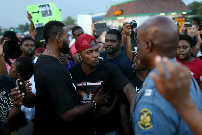 . Demonstrators speak to Capt. Ronald Johnson  (in blue uniform) of the Missouri State Highway Patrol, who was appointed by the governor to take control of security operations in the city of Ferguson after the shooting death of Michael Brown, on August 17, 2014 in Ferguson, Missouri. Violent outbreaks have taken place in Ferguson since the shooting death of Michael Brown by a Ferguson police officer on August 9th.  (Photo by Joe Raedle/Getty Images)