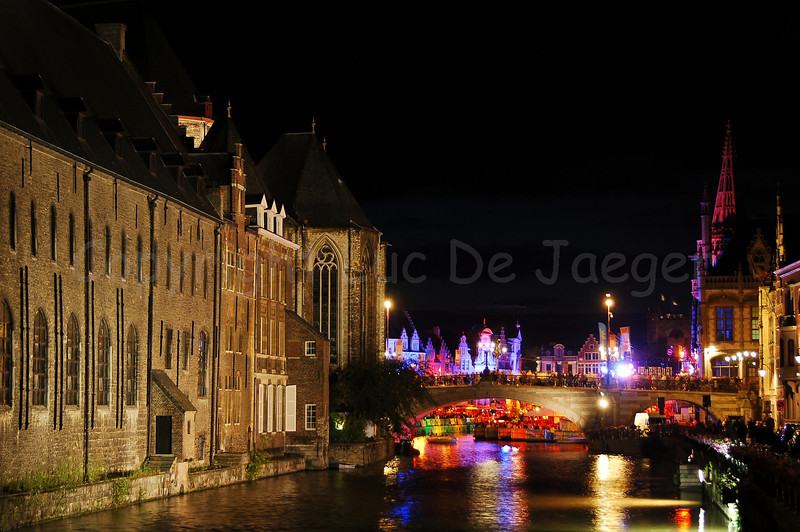 The highly colorful Polé Polé Festival during the Ghent Festivities (Gentse Feesten) 2009 in Ghent (Gent), Belgium is one of the many attractions bringing thousands of people to the place between Graslei and Korenlei. Photo of the St Michielsbrug (St Michael's bridge) with the colorful festival in the background, captured at night.