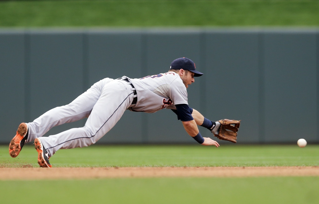 . Detroit Tigers shortstop Andrew Romine makes a futile dive for a sharp grounder off the bat of Minnesota Twins\' Eric Fryer in the third inning of a baseball game, Saturday,  Aug. 23, 2014, in Minneapolis. (AP Photo/Jim Mone)