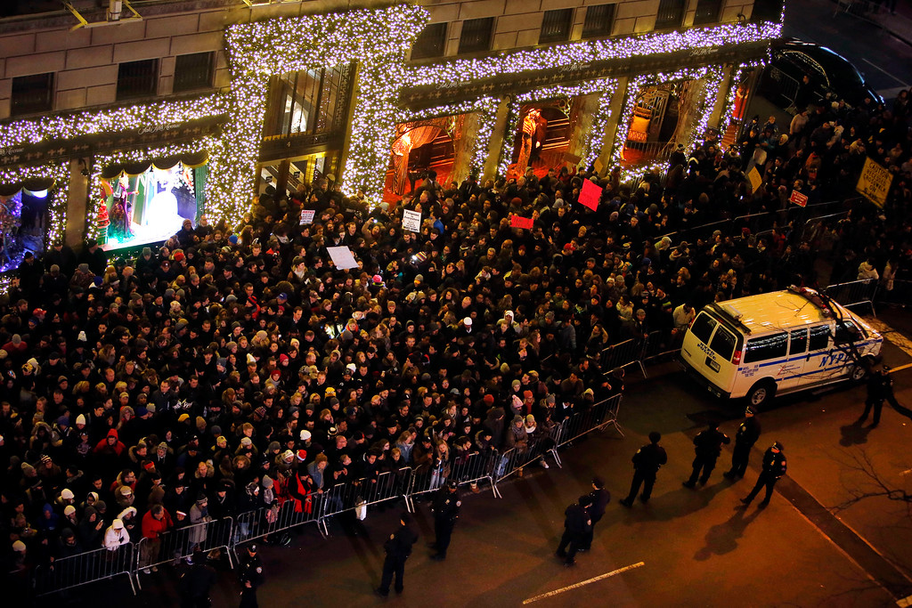 . A group of protesters with signs, rear, rally against the decision not to indict the police officer involved in the death of Eric Garner as they mix with spectators near Rockefeller Center during a ceremony to light the Rockefeller Center Christmas Tree, Wednesday, Dec. 3, 2014, in New York. (AP Photo/Jason DeCrow)