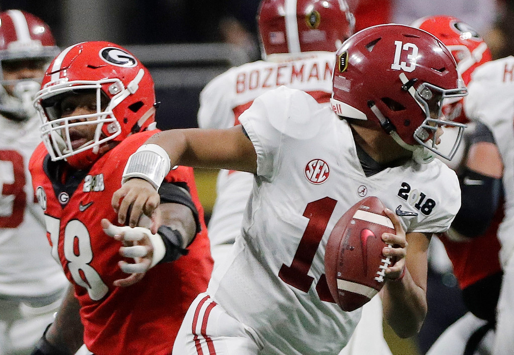 . Alabama\'s Tua Tagovailoa scrambles from Georgia\'s Trenton Thompson during the second half of the NCAA college football playoff championship game Monday, Jan. 8, 2018, in Atlanta. (AP Photo/David J. Phillip)