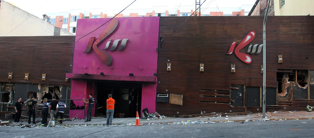 . Police investigators inspect the entrance of the Kiss nightclub in Santa Maria city, Rio Grande do Sul state, Brazil, Sunday, Jan. 27, 2013. Flames raced through the crowded nightclub in southern Brazil early Sunday, killing more than 230 people as panicked partygoers gasped for breath in the smoke-filled air, stampeding toward a single exit partially blocked by those already dead. (AP Photo/Nabor Goulart)