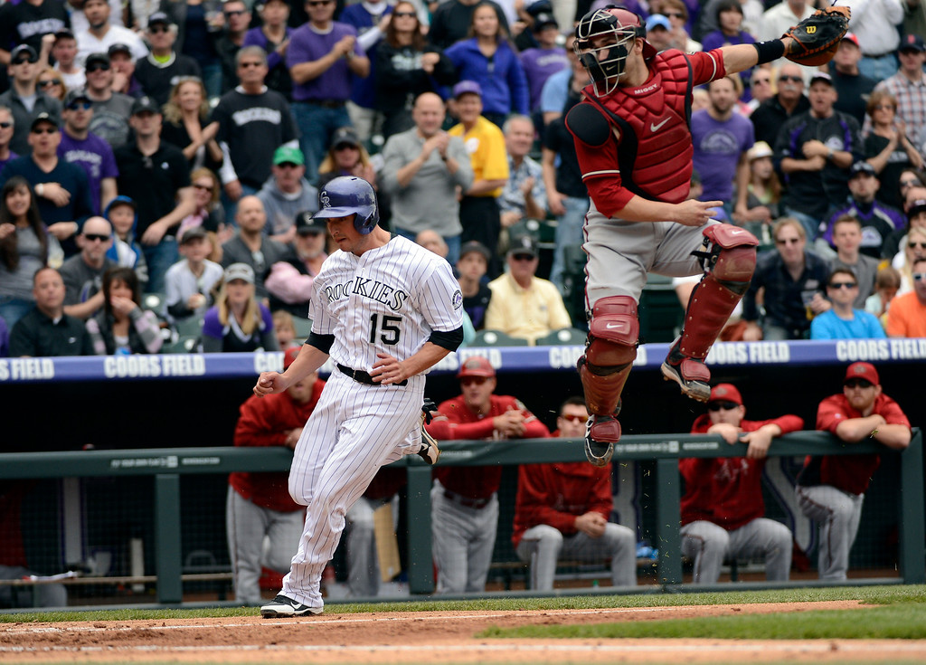 . DENVER, CO. - APRIL 21: Miguel Montero (26) of the Arizona Diamondbacks can\'t catch a high throw on the relay home as Jordan Pacheco (15) of the Colorado Rockies scores on a single by Carlos Gonzalez in the third inning April 21, 2013 at Coors Field. Eric Young Jr. (1) of the Colorado Rockies also scored on the play. (Photo By John Leyba/The Denver Post)