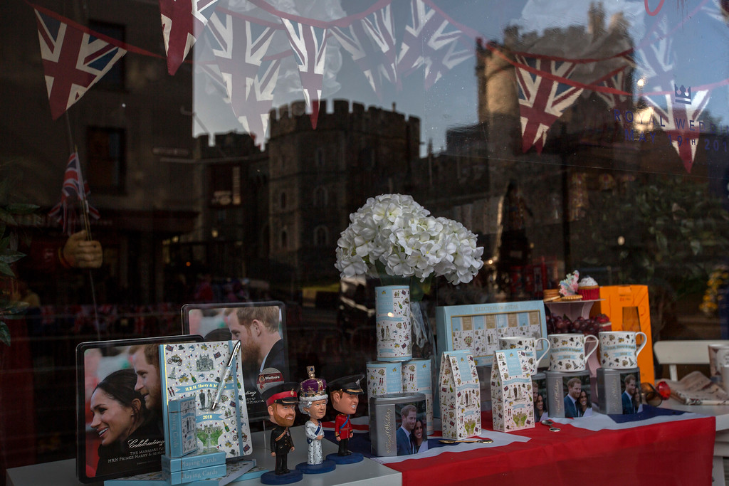 . Windsor Castle is reflected in a shop window selling souvenirs for Prince Harry and Meghan Markle\'s wedding, in Windsor, England, early Thursday, May 17, 2018. Preparations continue in Windsor ahead of the royal wedding of Britain\'s Prince Harry and Meghan Markle on Saturday May 19. (AP Photo/Emilio Morenatti)