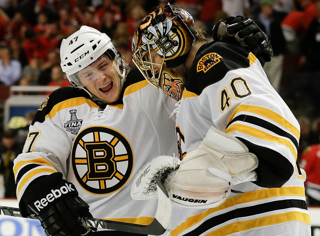 . Boston Bruins defenseman Torey Krug (47) celebrates with goalie Tuukka Rask (40) after the Bruins scored a goal against the Chicago Blackhawks in sudden death overtime during Game 2 of the NHL hockey Stanley Cup Finals, Saturday, June 15, 2013, in Chicago. The Bruins won 2-1. (AP Photo/Nam Y. Huh)