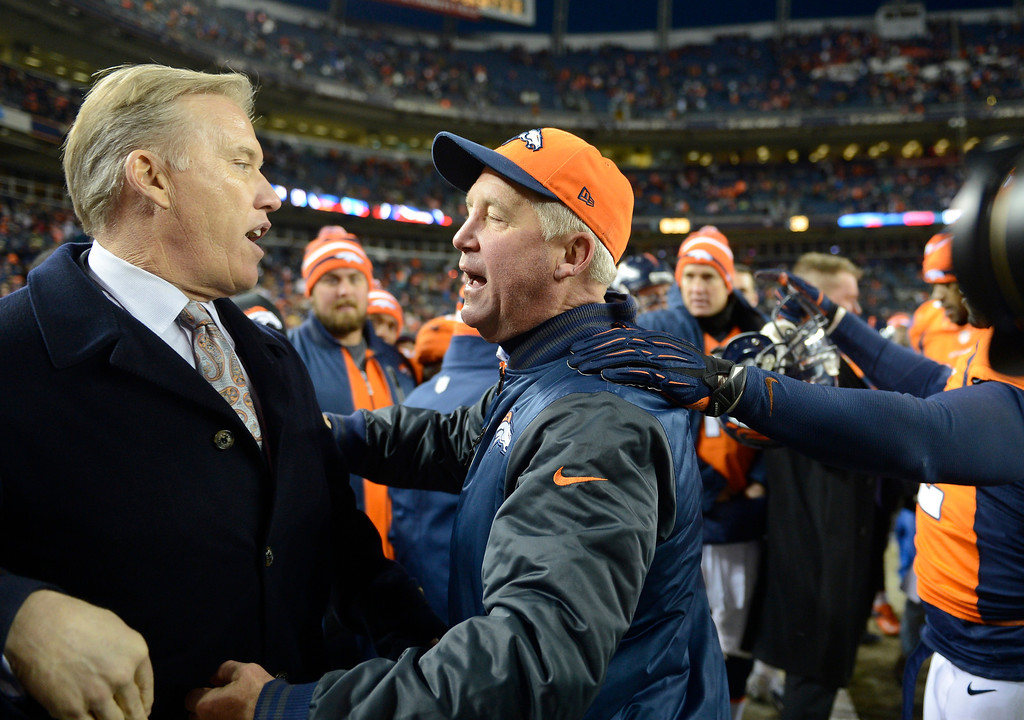 . John Elway gets a hug from Denver Broncos head coach John Fox as the Denver Broncos took on the Kansas City Chiefs at Sports Authority Field at Mile High in Denver, Colorado on December 30, 2012. Joe Amon, The Denver Post