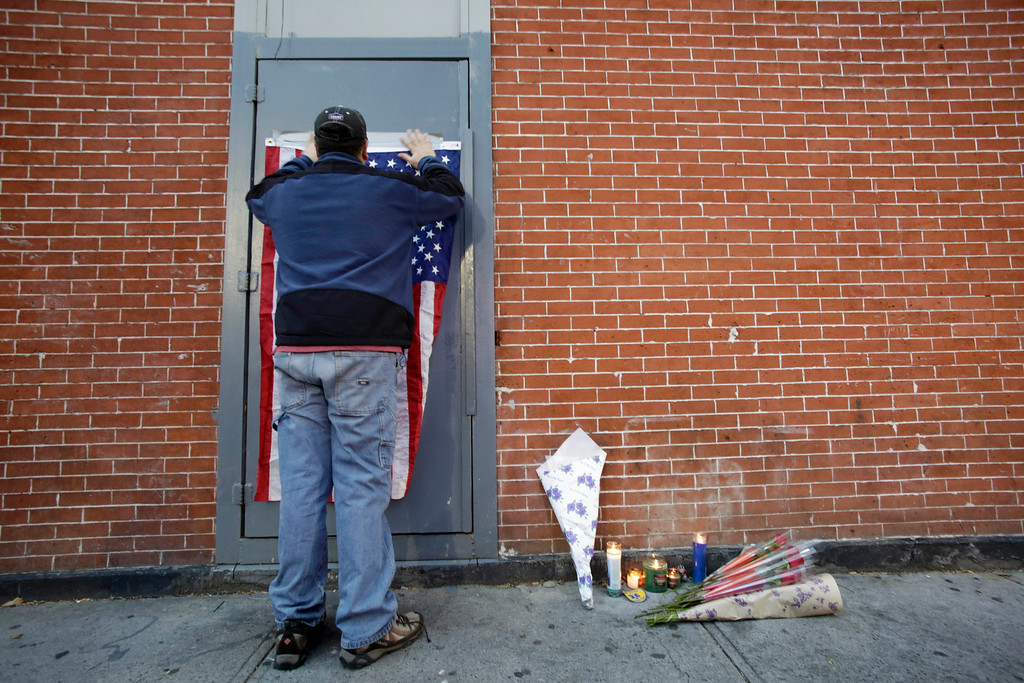 """. A man tapes an American flag to a doorway as part of a makeshift memorial for the two police officers who were shot there Saturday, Sunday, Dec. 21, 2014, in the Bedford-Stuyvesant neighborhood of the Brooklyn borough of New York. Ismaaiyl Brinsley, who vowed online to shoot two \""""pigs\"""" in retaliation for the police chokehold death of Eric Garner, ambushed two New York City officers in a patrol car Saturday and fatally shot them in broad daylight before running to a subway station and killing himself, authorities said. (AP Photo/Mark Lennihan)"""