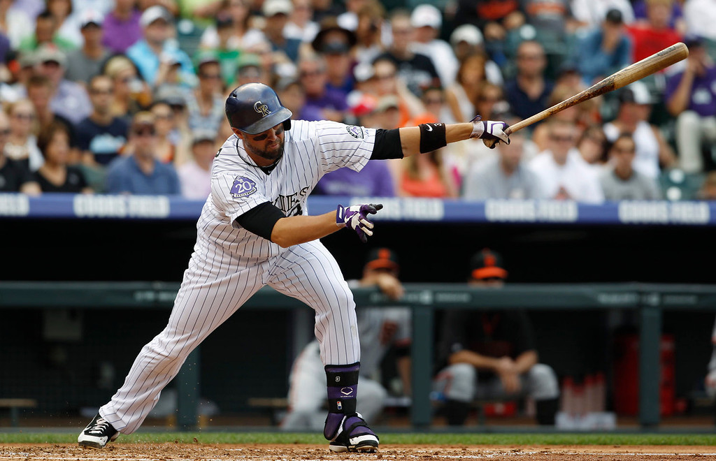 . Colorado Rockies\' Michael Cuddyer strikes out while swinging at a pitch against the San Francisco Giants in the first inning of a baseball game in Denver on Sunday, June 30, 2013.  (AP Photo/David Zalubowski)