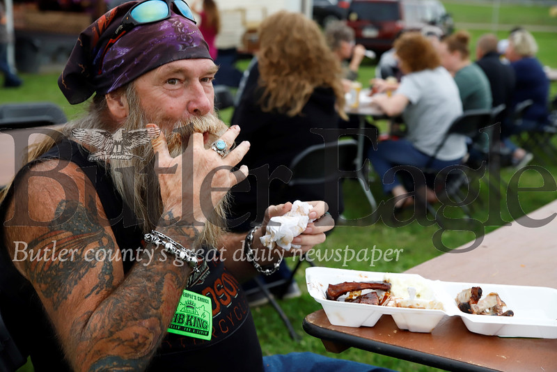 Mark Kampas takes a break from a Saturday motorcycle ride with friends to enjoy ribs at Butler's inaugural Rib & Music Festival. Seb Foltz/ Butler Eagle