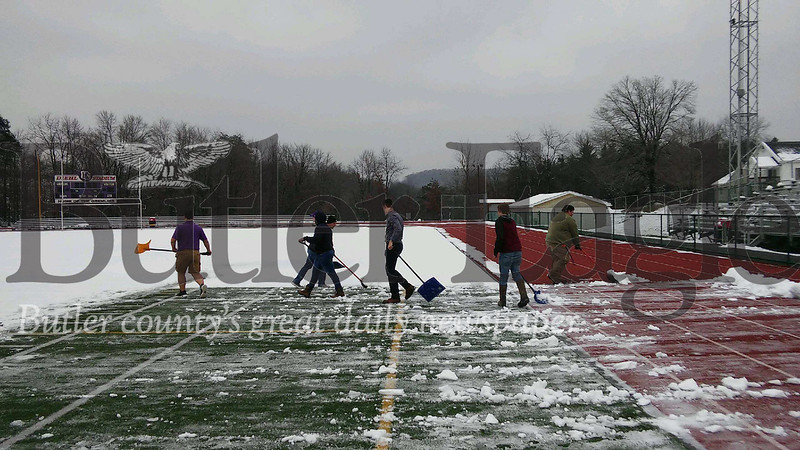 Members of the Karns City football team take to the Diego Stadium field to remove three inches of heavy, wet snow to get the surface playable for Monday's District 9 1A and 2A title games.