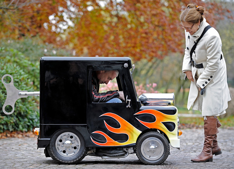 ". A woman watches British Perry Watkins sitting in his ""Wind Up\"" mini car on a street in Essen, Germany, Monday, Nov. 8, 2010. The car is listed in the Guinnes book of records as the world\'s smallest car with a license to drive on public streets. Just 41 inches high, 51 inches long and only 26 inches wide the mini always finds a parking space. It can drive 60 kph and even has security belts. The car will be shown at the motor show starting Nov. 27 in Essen.  (AP Photo/Martin Meissner)"