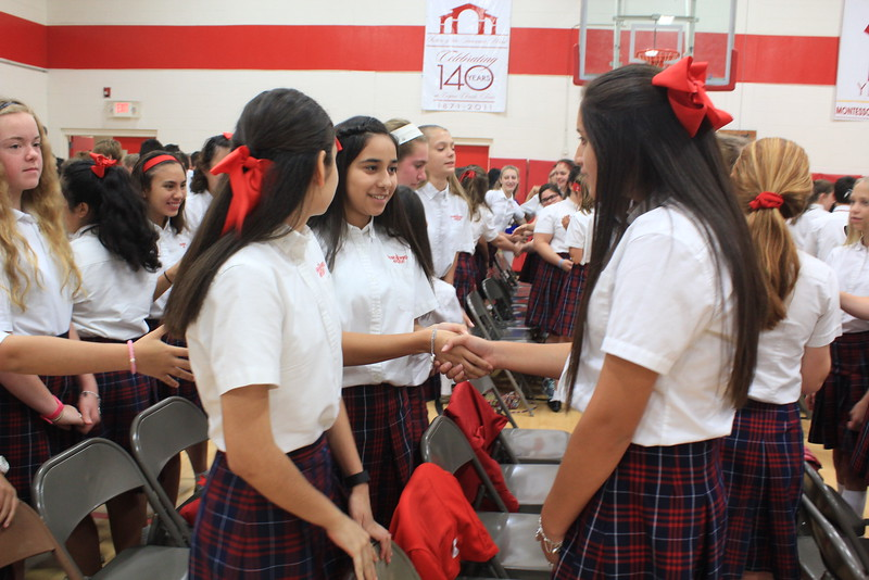 "IWA seventh graders shake hands and say ""Peace be with you"" to one another during a school Mass in honor of the Mother of God."