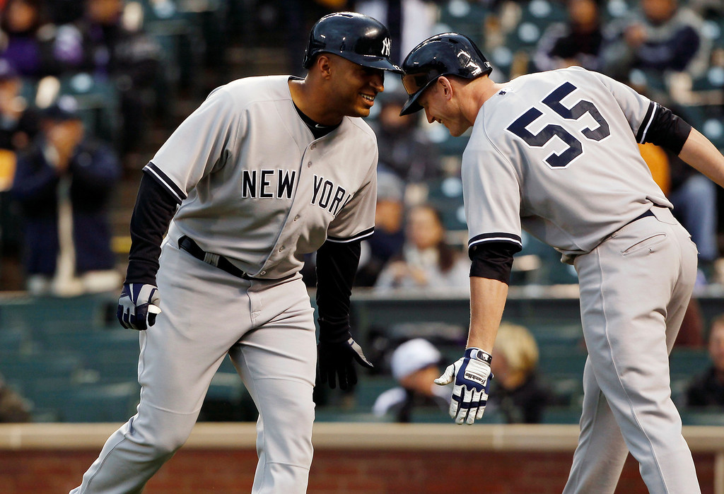 . New York Yankees\' Vernon Wells, left, is congratulated by teammate Lyle Overbay after hitting a two-run home run against the Colorado Rockies in the first inning of a baseball game in Denver on Wednesday, May 8, 2013. (AP Photo/David Zalubowski)