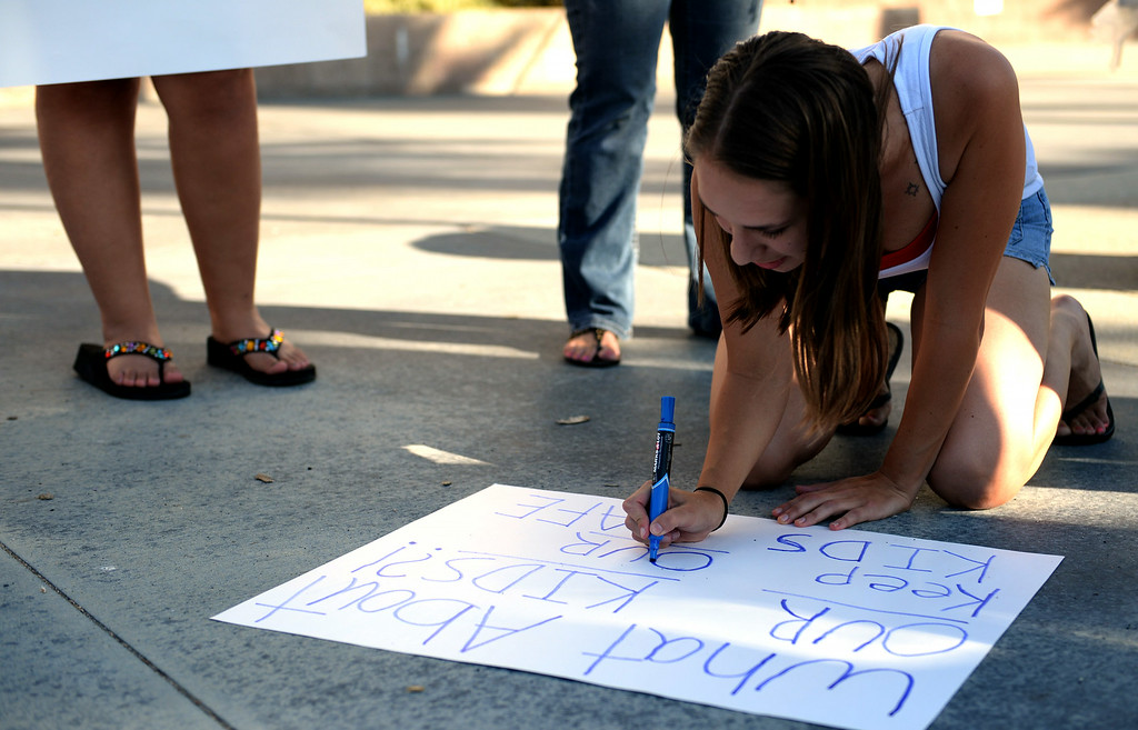 . Lori Espinosa, 22, of Murrieta, creates a sign prior to the start of a town hall meeting on Wednesday, July 2, 2014 at Murrieta Mesa High School in Murrieta, Ca. The meeting is being held in response to immigrants who were being processed through a Texas Border Patrol Station and delivered to the Murrieta Border Patrol Station on Tuesday. (Micah Escamilla/The Sun)