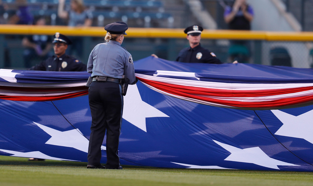 . Police officers unfurl an American flag to mark the anniversary of the 9/11 terrorist attacks during a ceremony before a baseball game against the Arizona Diamondbacks, Tuesday, Sept. 11, 2018, in Denver. (AP Photo/David Zalubowski)