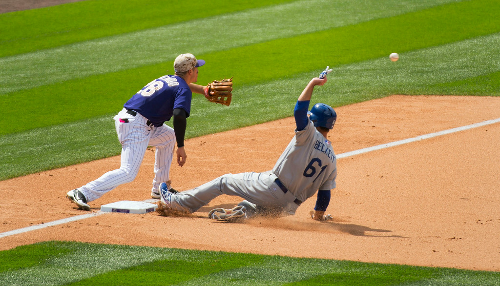 . Los Angeles Dodgers starting pitcher Josh Beckett (61) beats the throw to Colorado Rockies third baseman Nolan Arenado (28) on a throw from Colorado Rockies left fielder Corey Dickerson (6) July 6, 2014 at Coors Field. (Photo by John Leyba/The Denver Post)