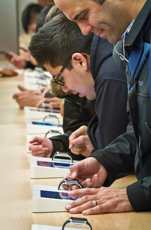 . Customers examine Apple\'s new watch, which could only be bought pre-order online, Friday, April 10, 2015, in New York. The first new gadget under CEO Tim Cook is selling in eight countries and Hong Kong, with shipments scheduled to start April 24.  (AP Photo/Bebeto Matthews)