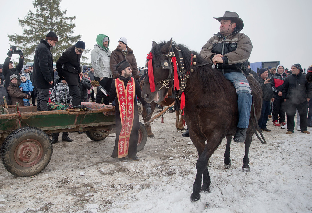 . An orthodox priest blesses horses before a traditional Epiphany celebration horse race in Pietrosani, Romania, Wednesday, Jan. 6, 2016. According to the local Epiphany traditions, following a religious service villagers get their horses blessed with Holy water then compete in a race. (AP Photo/Vadim Ghirda)